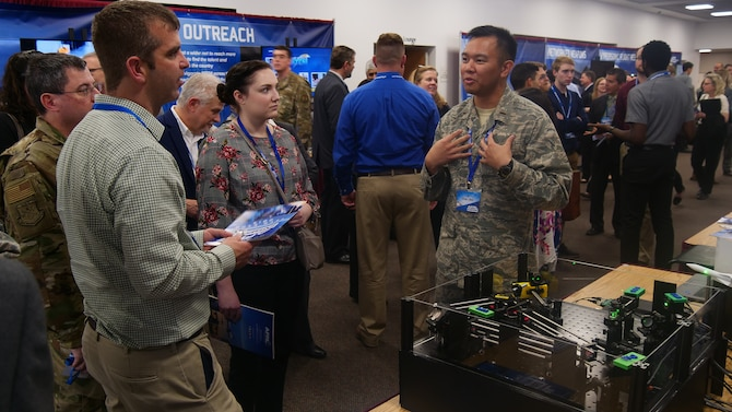 2nd Lt. J.D. Vela Cruz, an laser weapons & aerodynamics engineer from AFRL's Directed Energy Directorate, explains how directed energy amplifies speed, range, precision and accuracy to attendees at the AFRL 2019 Tech Expo event. (U.S. Air Force photo/Keith Lewis)
