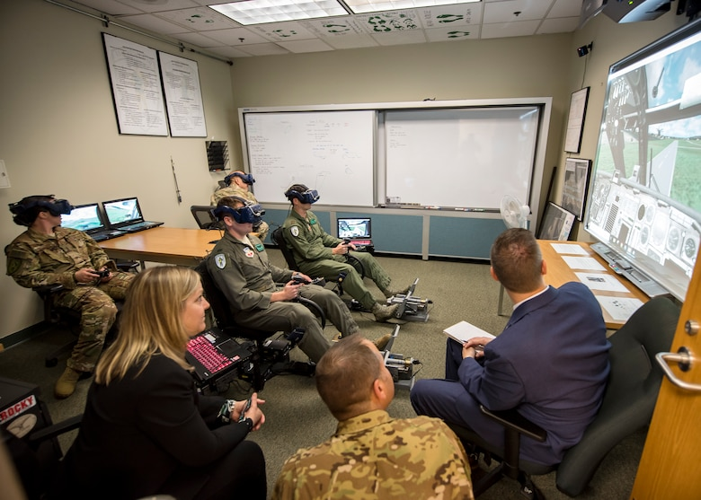 Pilots and Special Mission Aviators from the 41st Rescue Squadron (RQS), demonstrate their virtual reality flight simulator, May 16, 2019, at Moody Air Force Base, Ga. Dr. John Matyjas and Dr. Donna Joyce visited the 41st RQS to tour and assess their Virtual Reality flight simulator along with taking a fam flight on an HH-60G Pave Hawk. The visit is a part of an Air Force assessment of the possible implementation of VR in training. The 41st RQS VR flight simulator is an initiative that was selected at the Moody Air Force Base 2018 Spark Tank competition. (U.S. Air Force photo by Airman 1st Class Eugene Oliver)