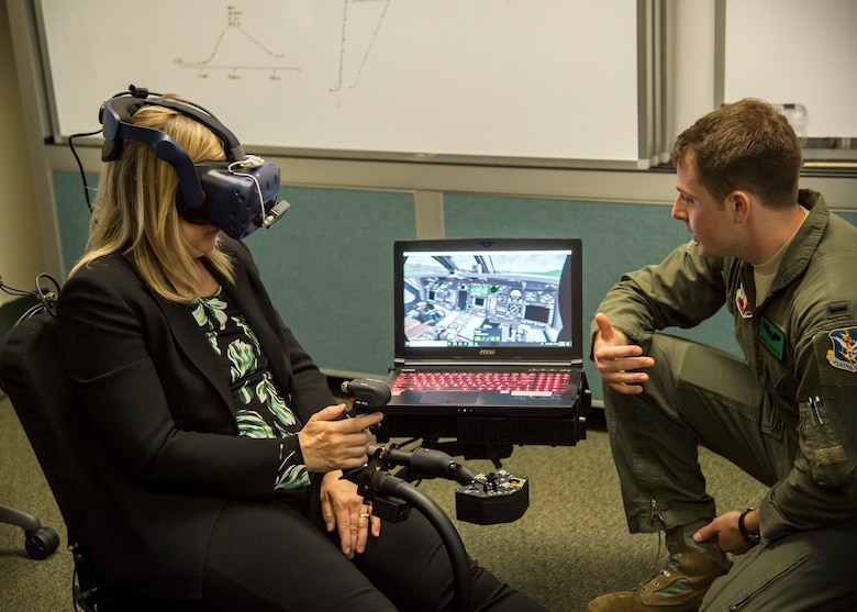 1st Lt. Patrick Livingston, 41st Rescue Squadron (RQS), HH-60G Pave Hawk co-pilot, gives instruction on their virtual reality flight simulator to Dr. Donna Joyce, science and technology advisor to Air Combat Command, May 16, 2019, at Moody Air Force Base, Ga. Dr. John Matyjas and Joyce visited the 41st RQS to tour and assess their VR simulator along with taking a fam flight on an HH-60G Pave Hawk. The visit is a part of an Air Force assessment of the possible implementation of VR in training. The 41st RQS VR flight simulator is an initiative that was selected at the Moody Air Force Base 2018 Spark Tank competition. (U.S. Air Force photo by Airman 1st Class Eugene Oliver)