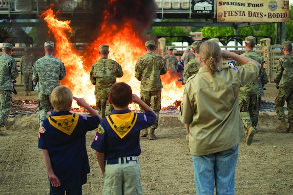 Boy scouts salute an American flag as it is retired in flames