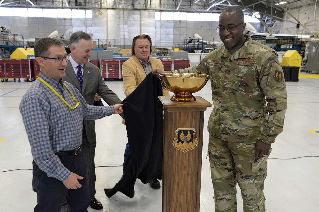 Stephen Zaiser, 571th Aircraft Maintenance Squadron director,  Eric Fox, Ogden Air Logistics Complex vice director, Troy Tingey, Union president, and Maj. Gen. Stacey Hawkins, OO-ALC commander, unveil the L-A-M-P Award trophy on May 9, at Hill Air Force Base, Utah. The new award is a traveling trophy which will be presented each month to the Complex's most outstanding unit.