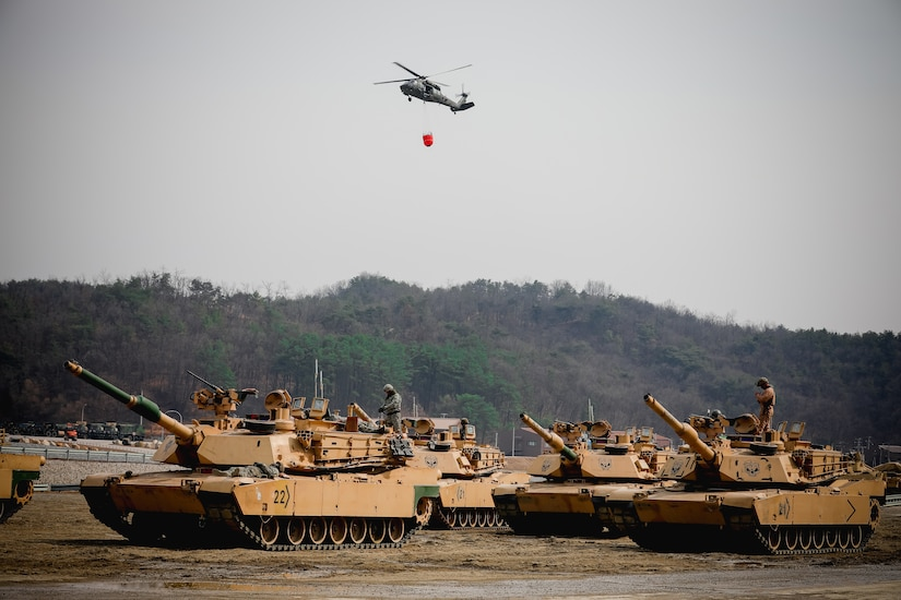 A helicopter flies over tanks.