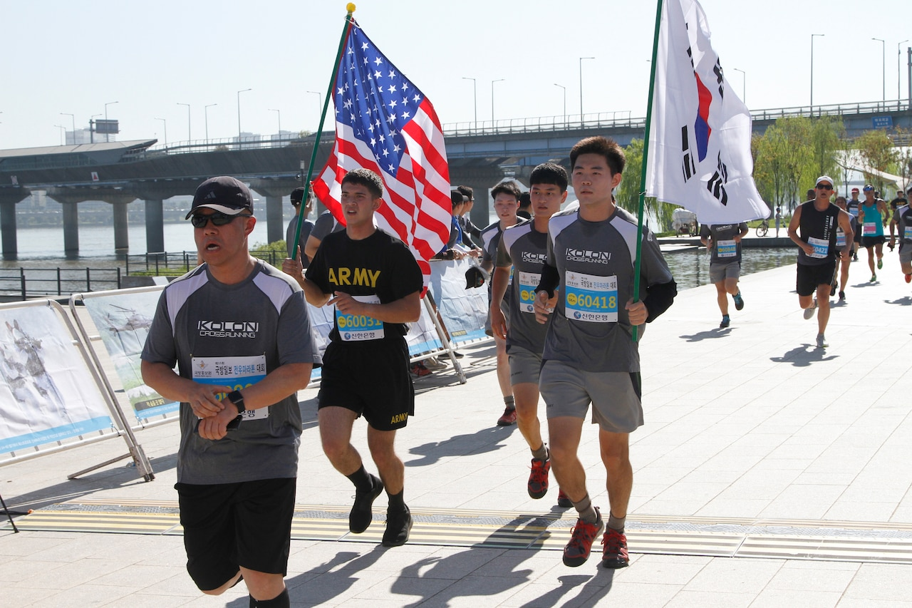 Runners take part in a race, with two carrying U.S. and South Korean flags.