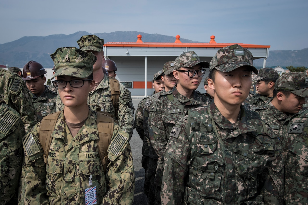 U.S. and South Korean sailors in camouflage uniforms stand in formation.