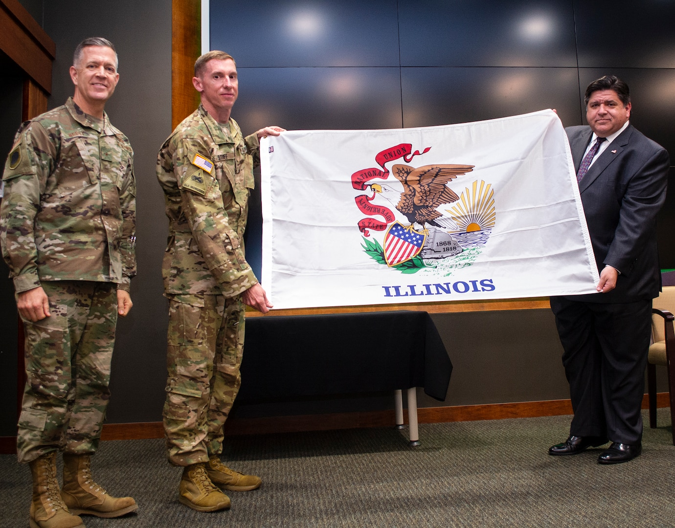 Illinois Governor JB Pritzker presents an Illinois flag to Chief Warrant Officer 5 Jason Stiff of Pawnee, Illinois, Commander, Detachment 5, Company A, 2nd Battalion, 245th Aviation Regiment, during the mobilization ceremony May 22 at Camp Lincoln, Springfield, Illinois. The unit will deploy to the Horn of Africa. Joining Pritzker and Stiff is Illinois Adjutant General Brig. Gen. Richard Neely. (U.S. Army photo by Barbara Wilson, Illinois National Guard Public Affairs Office.)