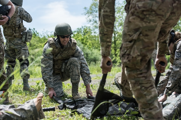 U.S. Airmen from the 193rd Special Operations Medical Group Detachment 1, Pennsylvania Air National Guard, prepare a litter for evacuation during Tactical Combat Casualty Care training.