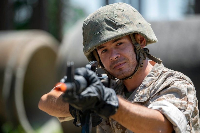 A man wearing camouflage and a military helmet aims a rifle.