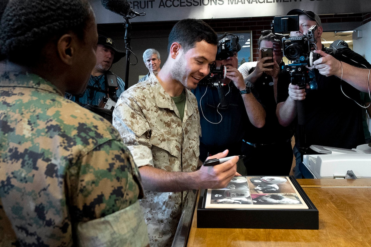 A man smiles while signing a photo.