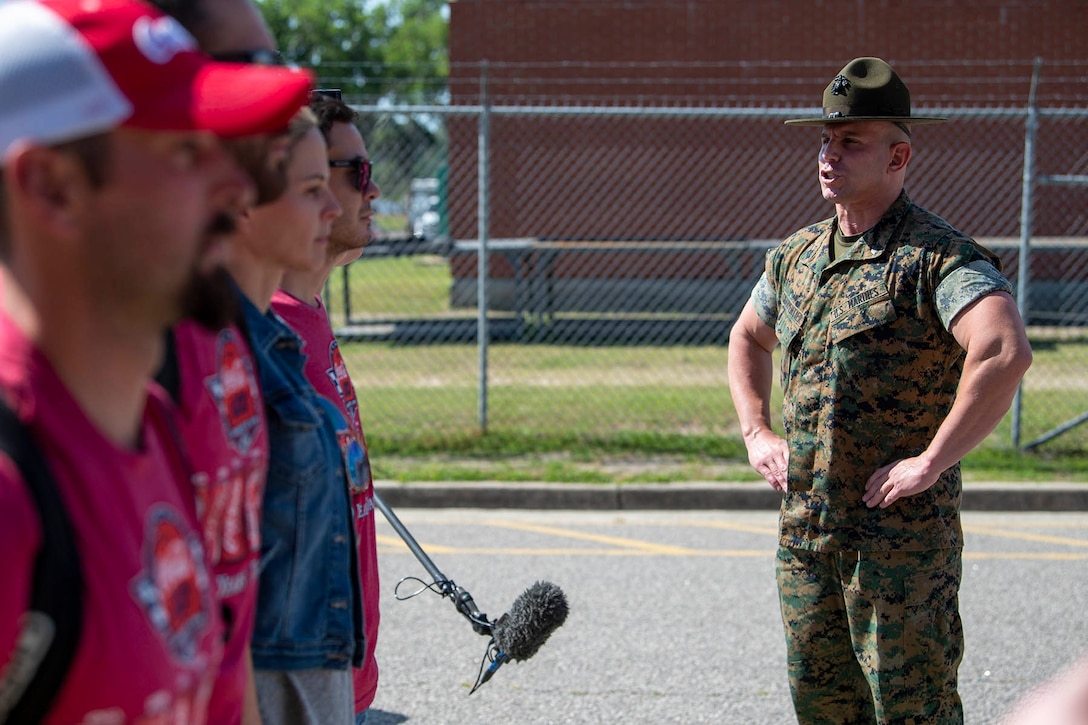 A Marine Corps drill instructor yells at four recruits.