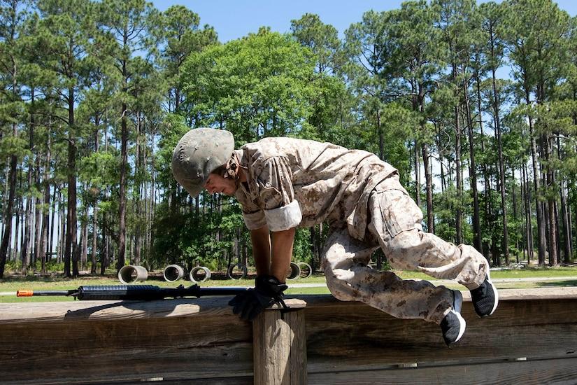 A man hops over a wooden beam.