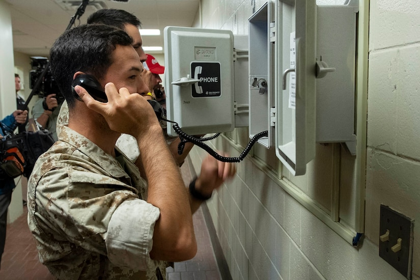A man holds a landline phone to his ear.