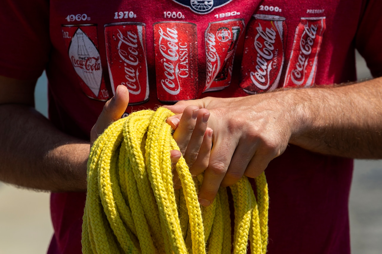 A man in a red T-shirt coils rope.