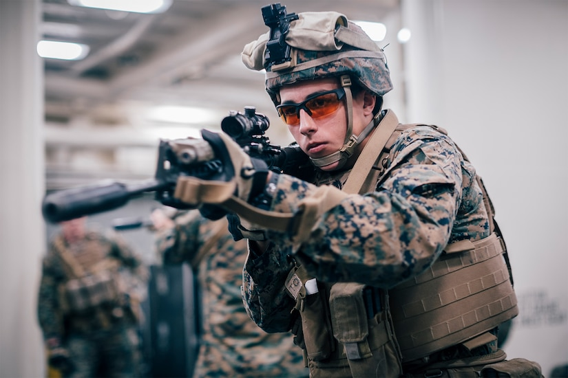 A Marine aims a rifle.
