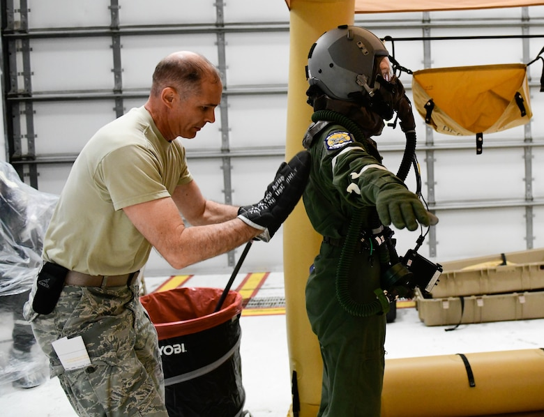 Master Sgt. Phil Walsh, aircrew flight equipment supervisor assigned to the 910th Operations Support Squadron, pats down Senior Airman Kaleb Walker, a loadmaster assigned to the 757th Airlift Squadron with a decontamination mitt on May 4, 2019.