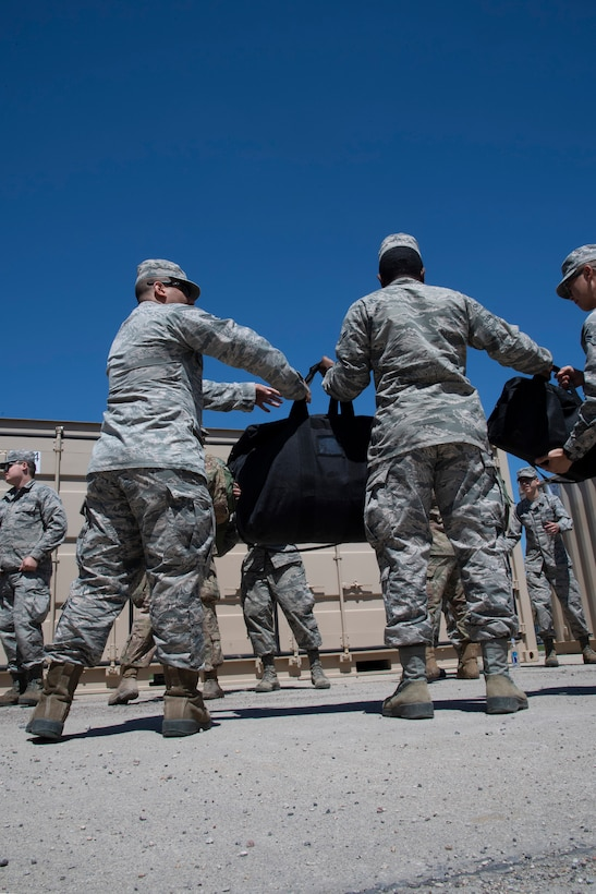 Grand Forks Air Force Base airmen work together to unload personal belongings and mission oriented protective posture gear May 20, 2019, to be used during exercise Summer Viking 19-01 on the National Air Guard Base in Fargo, North Dakota. Participants operated from a simulated contested base, in order to test capabilities and readiness in a deployed environment. (U.S. Air Force photo by Senior Airman Elora J. Martinez)