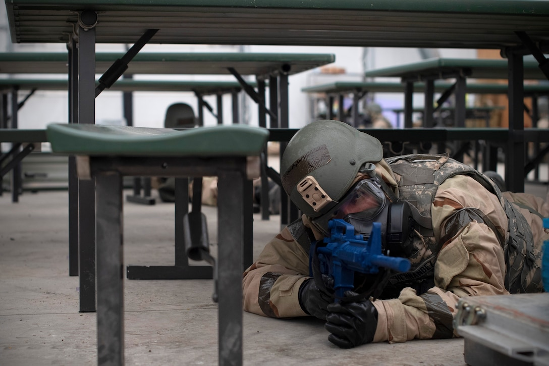 A Grand Forks Air Force Base airman lies in defense following an alarm sounding off May 22, 2019, during exercise Summer Viking 19-01 on the Air National Guard Base in Fargo, North Dakota. Alarms, simulated explosions and adversaries were all part of training for those who took part in the 4-day exercise which focused on practicing deployed readiness. (U.S. Air Force photo by Senior Airman Elora J. Martinez)