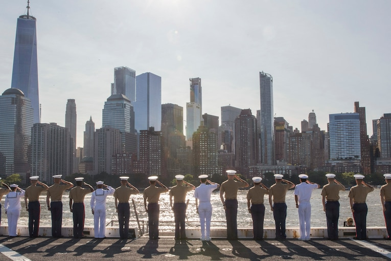 Sailors and Marines salute from a ship's deck while facing the New York City skyline.