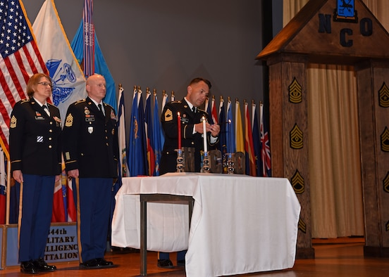 U.S. Army Master Sgt. Lorie Jansen, Master Sgt. Brandon White, and Master Sgt. Jason Piercy, members of the 344th Military Intelligence Battalion, light the candles at the Noncommissioned Officer Induction Ceremony at the base theater on Goodfellow Air Force Base, May 21, 2019. The candles symbolize the blood of soldiers who died for the country, the purity of the NCO, and the future of the NCO. (U.S. Air Force photo by Airman 1st Class Ethan Sherwood/Released)