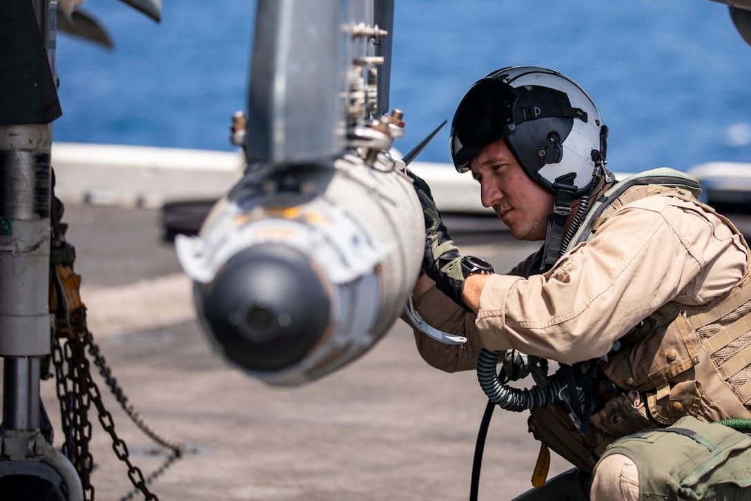 A crouching Marine checks a munition loaded on an aircraft.