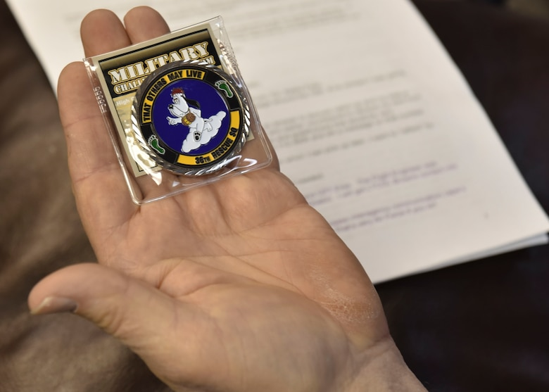 Karl Shoemaker holds a 36th Rescue Squadron coin
