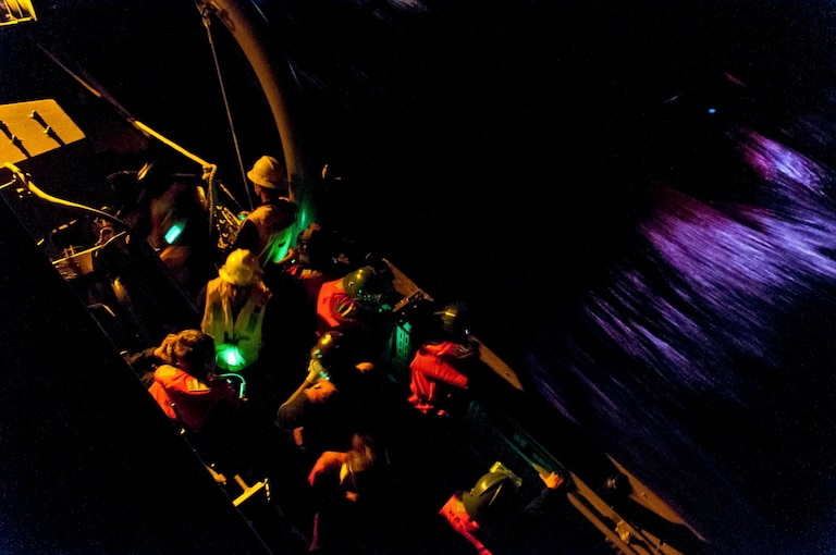 Sailors in multiple colors man a craft on the ocean at night.