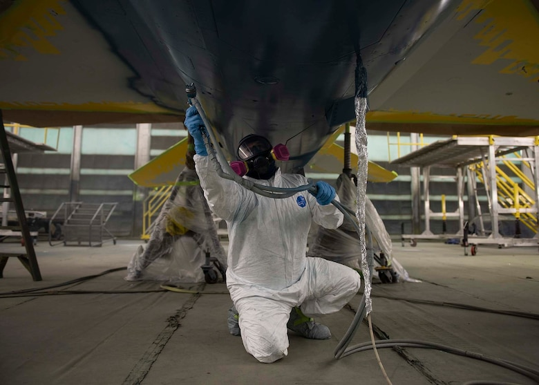 A civilian sprays paint on the bottom of a F-16 Fighting Falcon fighter jet.