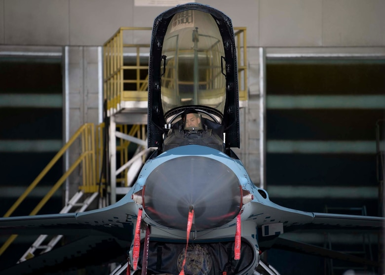 An Airman sits in the cockpit of an F-16 Fighting Falcon fighter jet.