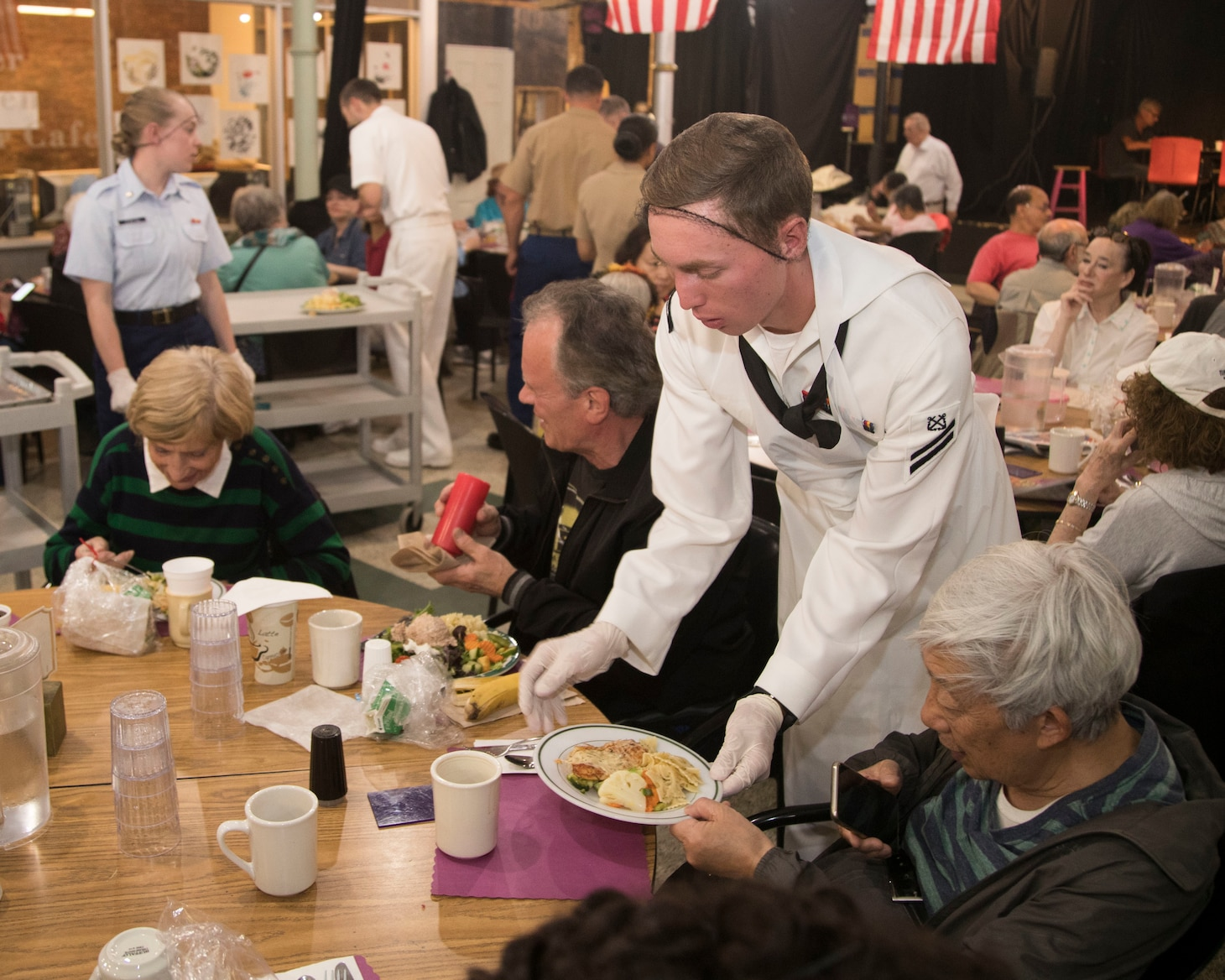A U.S. Sailor serves food to elderly patients at the at Burden Senior Center during Fleet Week New York 2019.
