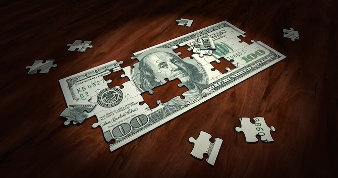 $50 bill as unassembled puzzle on wooden table