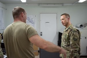 Maj. Adam Frost, 380th Expeditionary Medical Group physical therapist, listens to a patient about his back pain May 17, 2019 at Al Dhafra Air Base, United Arab Emirates. The base physical therapy team went to the maintenance and operations side of the base to visit multiple maintainers on-site. (U.S. Air Force photo by Staff Sgt. Chris Thornbury)