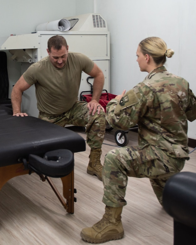 Senior Airman Tanita Frayne, right, 380th Expeditionary Medical Group physical therapist technician, demonstrates a mobility exercise for a patient May 17, 2019 at Al Dhafra Air Base, United Arab Emirates. After a treatment the technician educates the patient on mobility exercises to strengthen the problem area and prevent future injuries. (U.S. Air Force photo by Staff Sgt. Chris Thornbury)