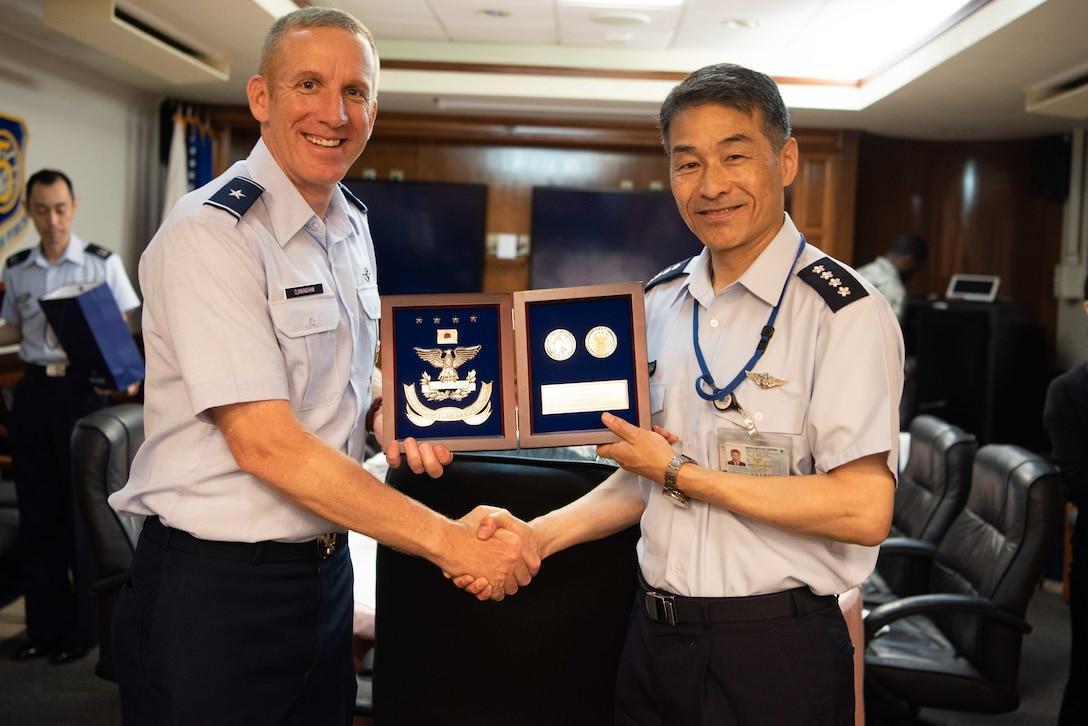 U.S. Air Force Brig. Gen. Case Cunningham, 18th Wing commander, and Japan Air Self -Defense Force Chief of Staff Gen. Yoshinari Marumo, exchange gifts during a visit to Kadena Air Base, Japan May 21, 2019.