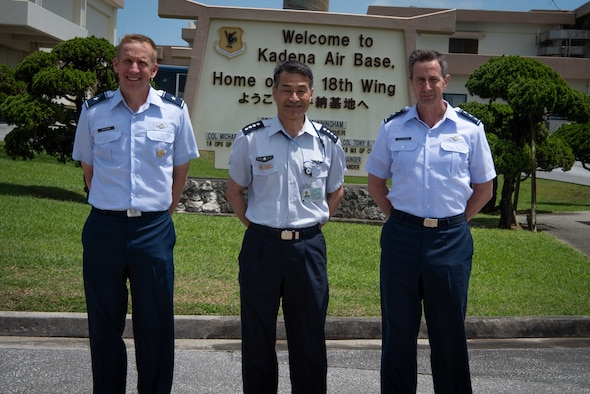 U.S. Air Force Brig. Gen. Case Cunningham, 18th Wing commander (left), Japan Air Self -Defense Force Chief of Staff Gen. Yoshinari Marumo (middle), and Lt. Gen. Kevin B. Schneider, U.S. Air Forces Japan commander, pose for a photo in front of the 18th Wing welcome sign May 21, 2019, at Kadena Air Base, Japan.