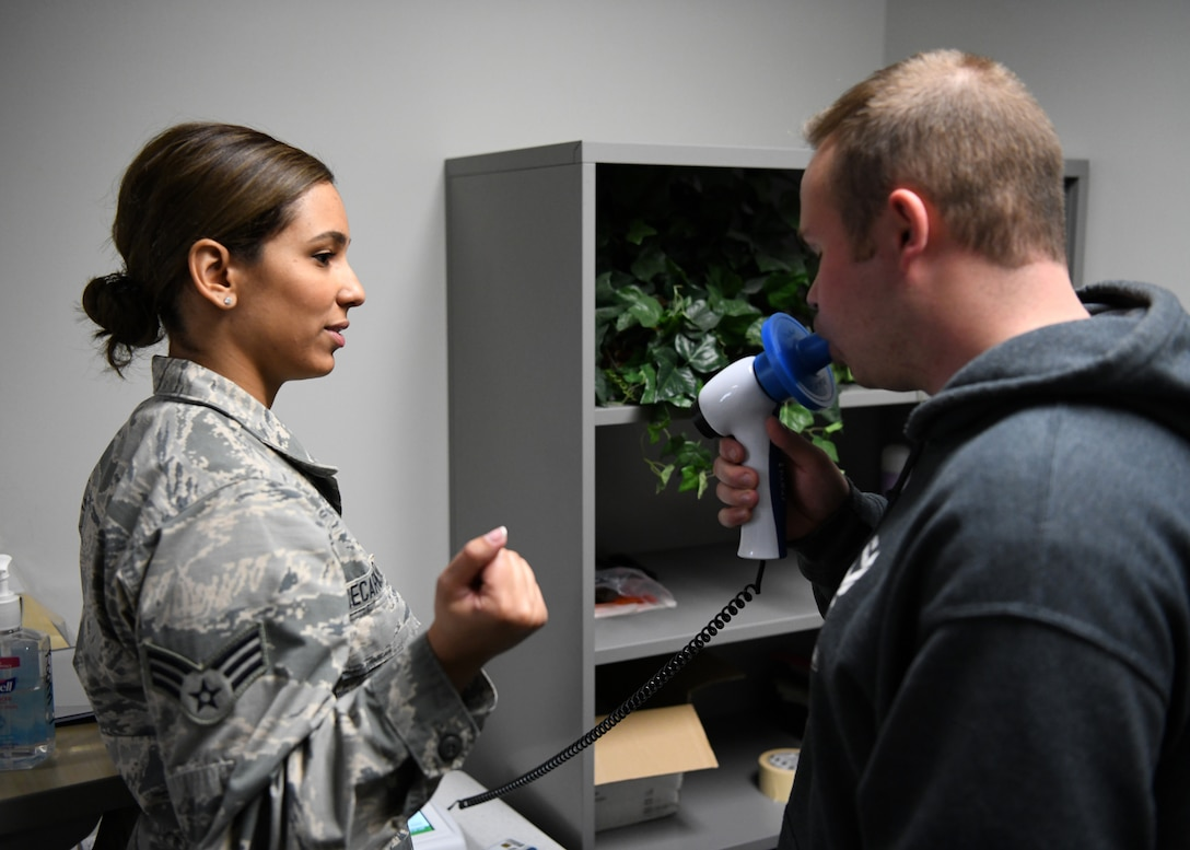 Senior Airman Ana Decarvalho, 104th Medical Group aerospace medical technician, performs a spirometry test with Joe D'Astous, 104th Fighter Wing student flight member at Barnes Air National Guard Base, Massachusetts, May 18, 2019. Decarvalho recently graduated from Quinsigamond Community College's Registered Nurse program. (U.S. Air National Guard photo by Airman 1st Class Randy Burlingame)