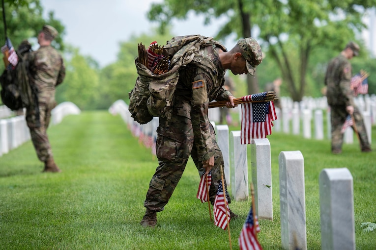 A soldier carries mini American flags at a cemetery.