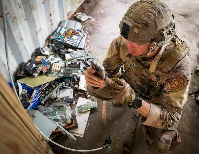 An airman uses his phone to take a photo of an electrical box during the Explosive Ordnance Disposal Warfighter Challenge