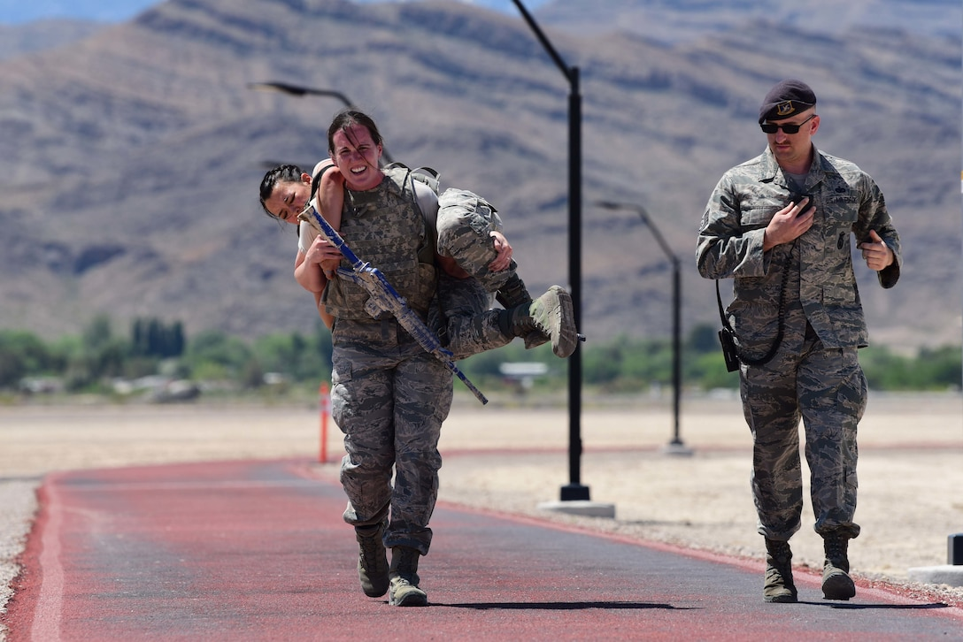 Capt. Sarah, 799th Air Base Squadron Force Support Flight chief, carries 1st Lt. Ryann, 799th ABS Military Personnel Flight commander, during a police week defender challenge
