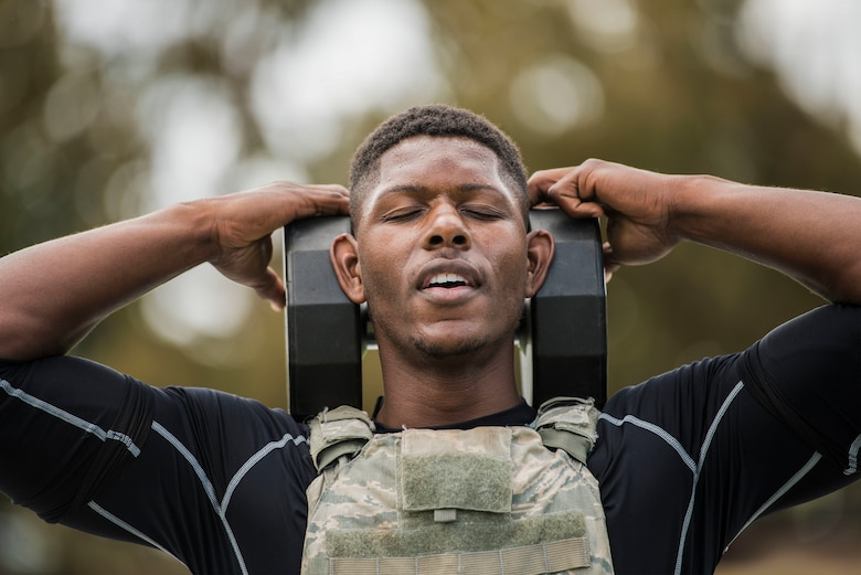 First Lt. Xavier Jones, 17th Training Squadron test team project manager, performs box steps with a 50 pound weight during the police week warrior workou