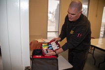 "Greg Kunkle, Emergency Medical Services Chief for Fire and Emergency Services displays one of the four trauma kits contained within the Public Access Stations which will be located throughout Marine Corps Logistics Base Barstow, Calif. May 22. The kits are part of the ""Stop the Bleed"" campaign embraced by fire departments throughout the state, and contain all of the necessary equipment to render first aid during emergency incidents."