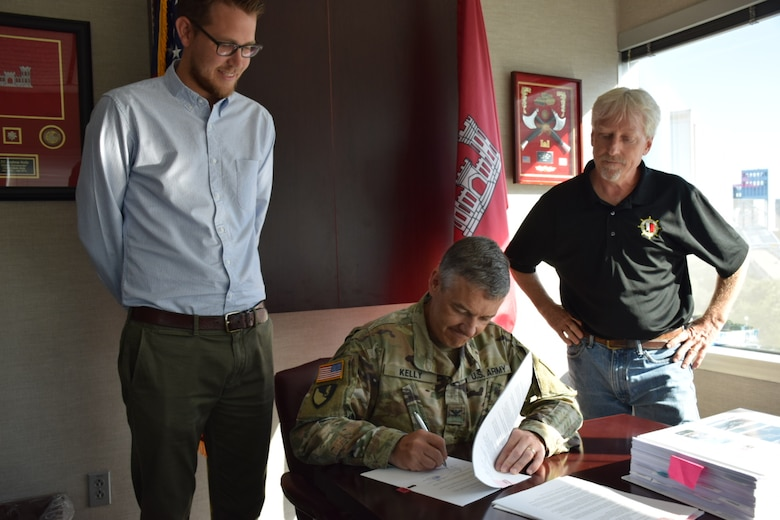 Col Kelly sitting at his desk signing a document while two Jacksonville district employees stand by his sides