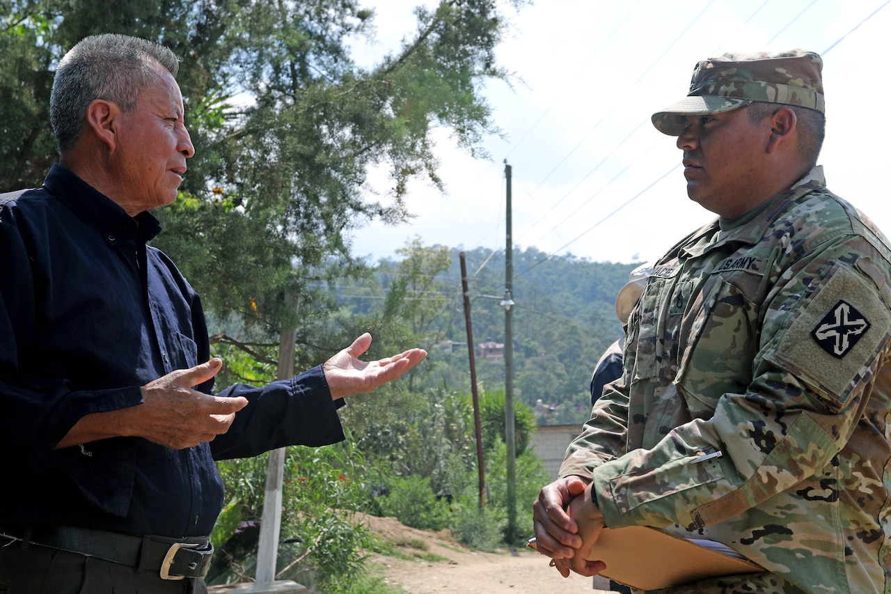 A man and a soldier converse outdoors.