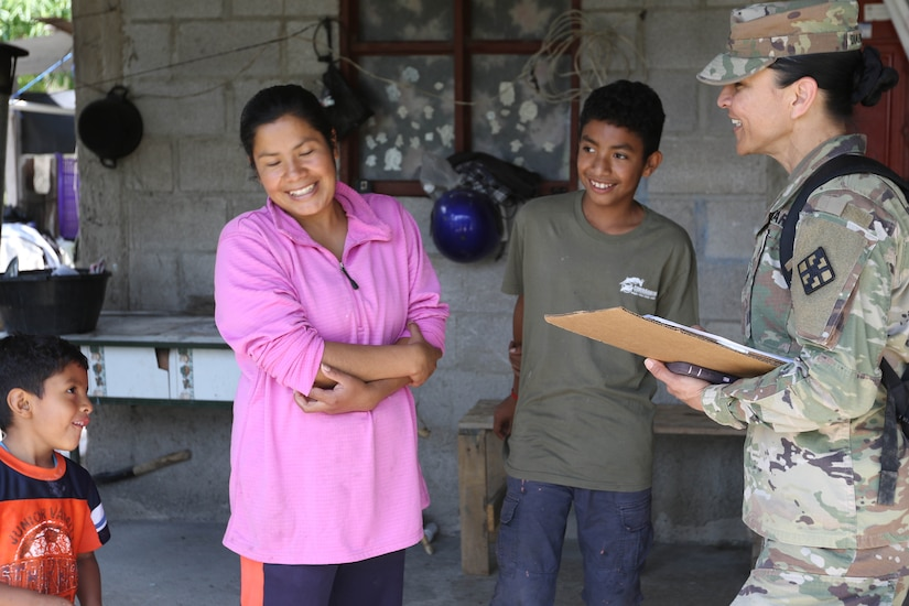 A soldier with a clipboard talks with a woman and her children.