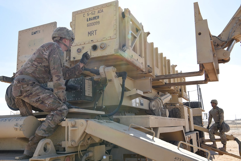 Soldiers reload a missile.