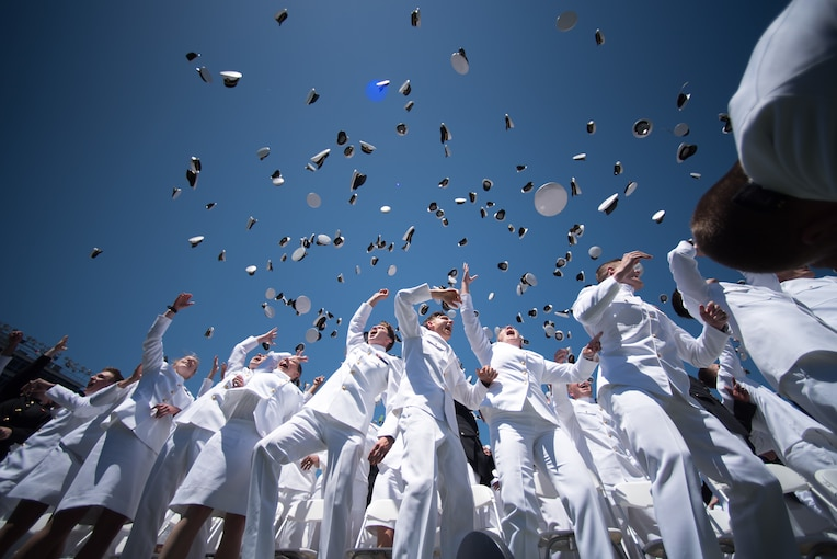 A group of graduating sailors toss hats in the air.