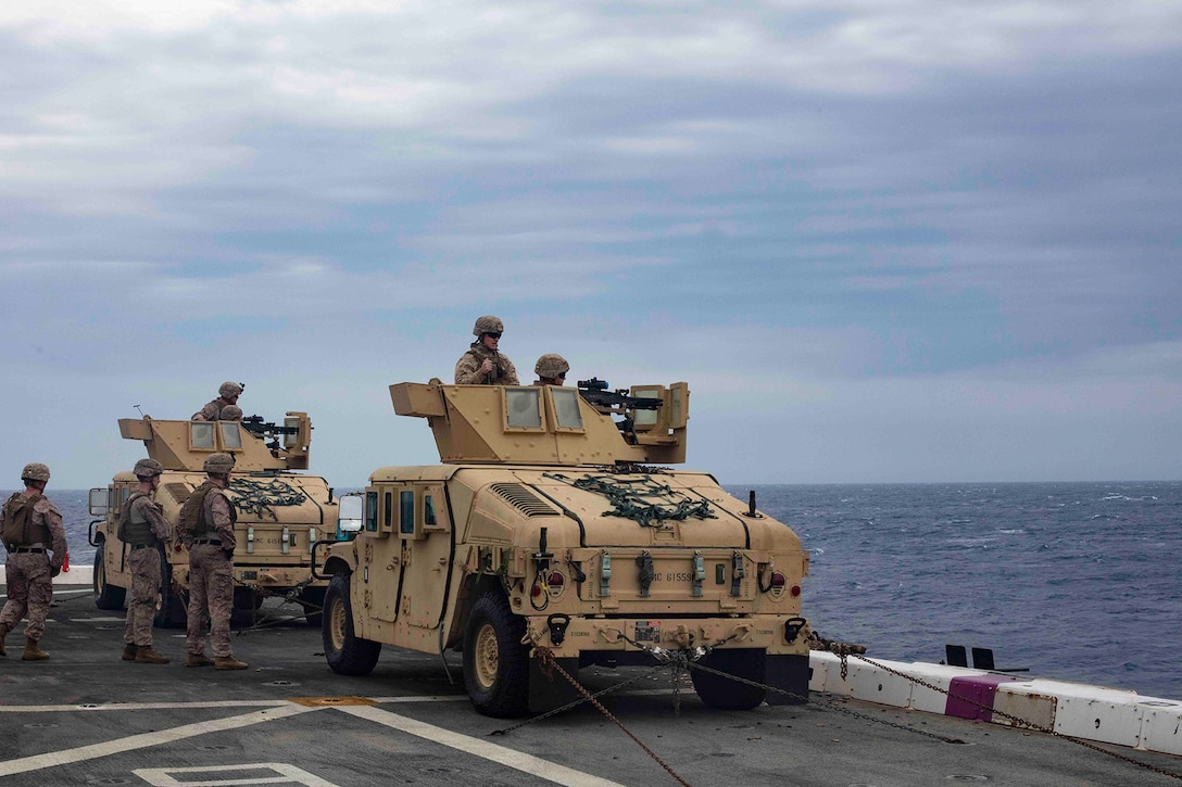 Marines in vehicle fire machine guns out to sea.