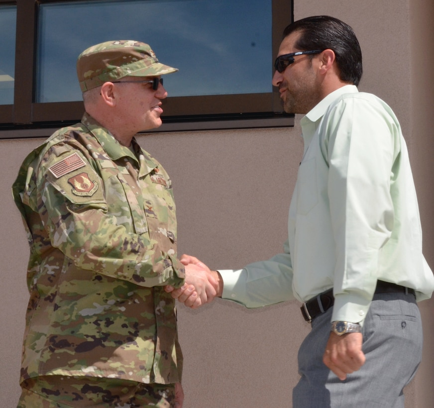 Filemon Gallegos, project manager, USACE, receives a commander's coin from Col. Eric J. Felt, commander, Space Vehicles Directorate, during the NTSIL ribbon-cutting ceremony at KAFB on March 26, 2019.