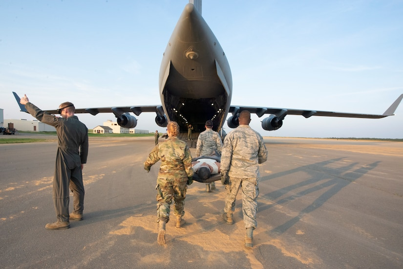 315th Aeromedical Evacuation Squadron ground crew members carry a simulated patient on a litter to board a Charleston-based C-17 Globemaster III during the Palmetto Challenge Exercise May 22 near Pope Field, North Carolina.