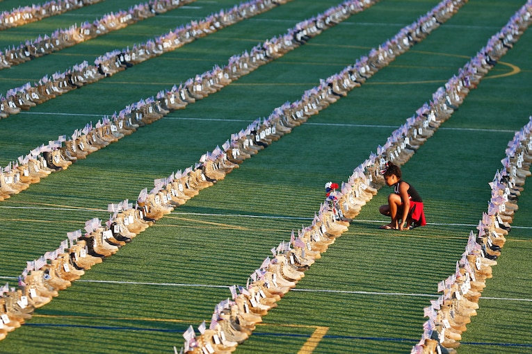 A young girl examines boots displayed in rows on a field.