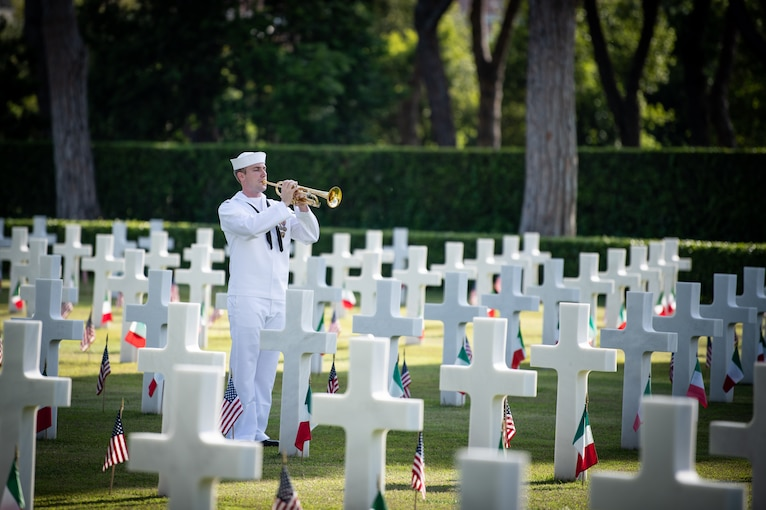 A lone bugler stands among gravestones in a cemetery.