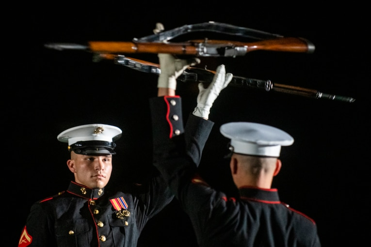 Marines spin guns above their heads during a performance.